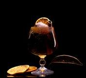 Cóctel con el palillo del hielo, del limón y de canela en un vidrio en un fondo negro foto de archivo
