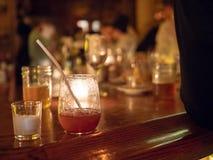 Cóctel con sabor a fruta en una barra iluminada por velas imagen de archivo libre de regalías