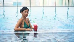 Cóctel de consumición de la muchacha bastante atractiva de los jóvenes en piscina almacen de video