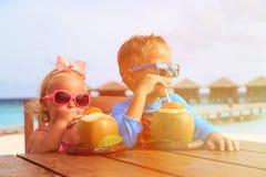 Cóctel de consumición del coco del niño pequeño y de la muchacha encendido fotos de archivo