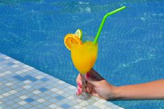 Cóctel de consumición de la belleza femenina real cerca de la piscina Fotos de archivo