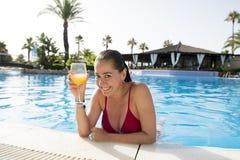 Cóctel de consumición de la mujer atractiva feliz del lation en piscina fotos de archivo
