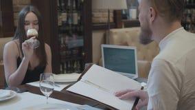 Cóctel de consumición de la mujer morena del encanto que se sienta en la tabla con su novio barbudo que escucha él y la sonrisa almacen de metraje de vídeo