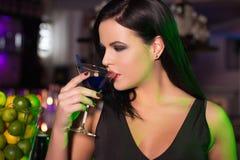 Cóctel de la bebida de la mujer en barra en la noche fotografía de archivo libre de regalías