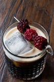 Cóctel de la cerveza negra/oscura con las zarzamoras y el hielo en superficie de madera fotos de archivo