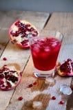 Cóctel de la granada con hielo y fruta en la tabla de madera Suavidad de restauración o alcohólico de la bebida del verano Imagen de archivo libre de regalías
