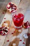 Cóctel de la granada con hielo y fruta en la tabla de madera Suavidad de restauración o alcohólico de la bebida del verano Foto de archivo