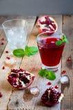 Cóctel de la granada con la menta y la fruta del hielo en la tabla de madera Suavidad de restauración o alcohólico de la bebida d Foto de archivo
