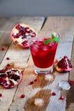 Cóctel de la granada con la menta y la fruta del hielo en la tabla de madera Suavidad de restauración o alcohólico de la bebida d Fotografía de archivo