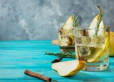 Cóctel de la pera con el ron, el licor, las rebanadas y el romero en una tabla de madera azul, foco selectivo de la pera foto de archivo libre de regalías