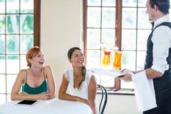 Cóctel de la porción del camarero a las mujeres en restaurante Imagen de archivo