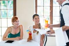 Cóctel de la porción del camarero a las mujeres en restaurante Imagen de archivo libre de regalías
