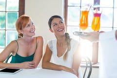 Cóctel de la porción del camarero a las mujeres en restaurante Fotografía de archivo