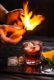 Cóctel de Mezcal Negroni Aperitivo italiano ahumado Cáscara de naranja flameada Foto de archivo libre de regalías