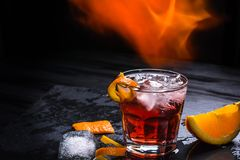 Cóctel de Mezcal Negroni con las llamas Aperitivo italiano ahumado Anaranjado - macro Foto de archivo