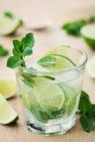 Cóctel de Mojito con las hojas de la cal, del hielo y de menta en la tabla de madera, bebida del verano Imagenes de archivo