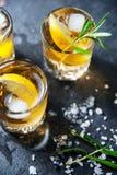 Cóctel del alcohol con hielo y romero que fuma en el limón oscuro de la tabla fotografía de archivo