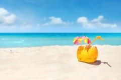 Cóctel del coco con la paja y los paraguas coloridos en una playa Foto de archivo
