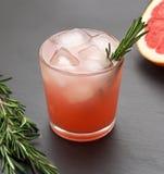 Cóctel del pomelo del verano con romero e hielo en fondo de la pizarra Imagenes de archivo