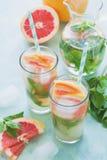 Cóctel del pomelo del refresco con la menta en fondo del color de la menta Bebida sana del verano de la fruta cítrica Imagen de archivo