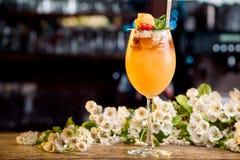 Cóctel del verano adornado con las bayas y la menta en un contador de la barra en un fondo floral Imagen de archivo
