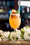 Cóctel del verano adornado con las bayas y la menta en un contador de la barra en un fondo floral Fotos de archivo