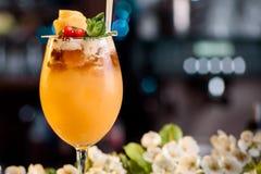 Cóctel del verano adornado con las bayas y la menta en un contador de la barra en un fondo floral Fotografía de archivo