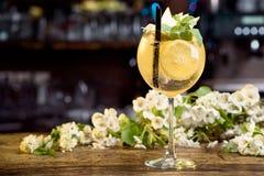 Cóctel del verano adornado con las peras de la menta, del limón y de las rebanadas en una tabla de madera en un fondo floral Imagenes de archivo