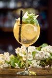 Cóctel del verano adornado con las peras de la menta, del limón y de las rebanadas en una tabla de madera en un fondo floral Imágenes de archivo libres de regalías