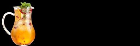 C?ctel en una garrafa de cristal con la naranja y bayas y jarabe dulce Refresco aislado en un fondo negro bandera imagen de archivo libre de regalías