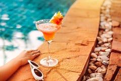Cóctel o jugo, gafas de sol del verano en la piscina foto de archivo