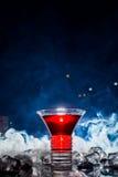 Cóctel rojo con el vapor del hielo, fondo azul foto de archivo