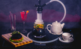 Cóctel rojo con la caldera, la hamburguesa y la cachimba Imagen de archivo libre de regalías
