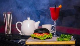 Cóctel rojo con la caldera y la hamburguesa Foto de archivo libre de regalías