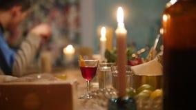 Cóctel rojo en un vidrio adornado con el limón en un contador en la barra con clase interior iluminada por la luz de una vela almacen de video