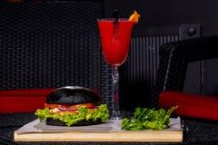Cóctel rojo y hamburguesa negra Fotos de archivo libres de regalías