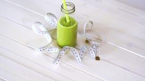 Cóctel sano del verde y del vegano con la cinta del centímetro en la tabla de madera blanca metrajes