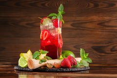 Cóctel stawberry de restauración brillante con la menta, el hielo, rebanadas de cal y pedazos de fresa Bebidas del verano Copie e Foto de archivo