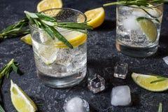 Cóctel tónico de la ginebra de la bebida alcohólica con el limón, el romero y el hielo en la tabla de piedra foto de archivo