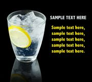 Cóctel transparente del alcohol con la rebanada del limón aislada en negro Imagen de archivo libre de regalías