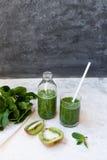 Cóctel verde en una botella y en un vidrio con espinaca, la menta, el romero, el kiwi y la manzana en un fondo ligero Foto de archivo