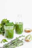 Cóctel verde en una botella y en un vidrio con espinaca, la menta, el romero, el kiwi y la manzana en un fondo ligero Foto de archivo libre de regalías