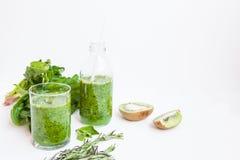 Cóctel verde en una botella y en un vidrio con la espinaca, menta, ro Imagen de archivo libre de regalías