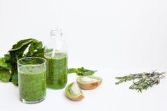 Cóctel verde en una botella y en un vidrio con la espinaca, menta, ro Fotografía de archivo libre de regalías