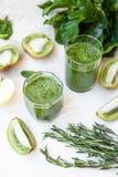 Cóctel verde en una botella y en un vidrio con la espinaca, menta, ro Foto de archivo