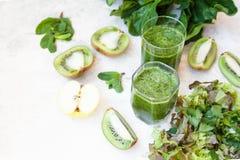 Cóctel verde en una botella y en un vidrio con la espinaca, menta, ro Foto de archivo libre de regalías