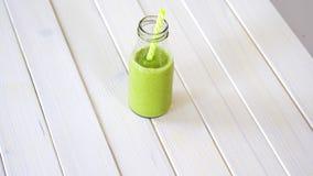 Cóctel verde sano de la fruta y del vegano en la tabla de madera blanca almacen de metraje de vídeo