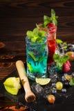 Cócteles brillantes con la menta, el hielo, las bayas y el carambola en el fondo de madera Bebidas del verano Copie el espacio Fotos de archivo