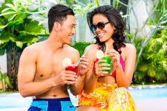 Cócteles de consumición de los pares asiáticos en la piscina Foto de archivo
