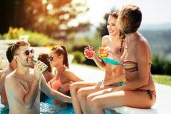 Cócteles de consumición de la gente joven en la piscina imagen de archivo libre de regalías